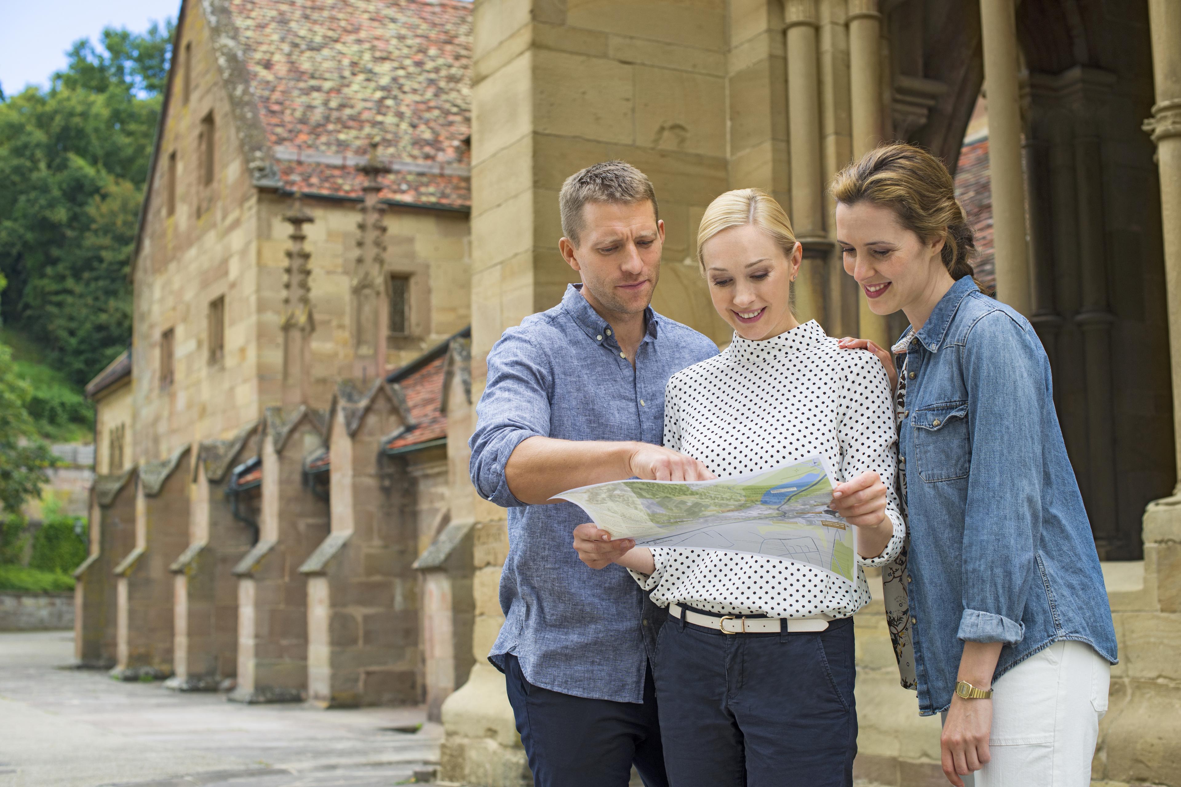 Drei Personen studieren eine Karte